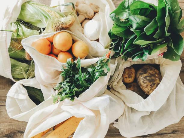 廚房裡餐桌上的環保棉袋中的新鮮蔬菜。生菜, 玉米, 馬鈴薯, 杏, 香蕉, rucola, 蘑菇市場。零垃圾購物概念。  禁止塑膠 - 有機食品 個照片及圖片檔