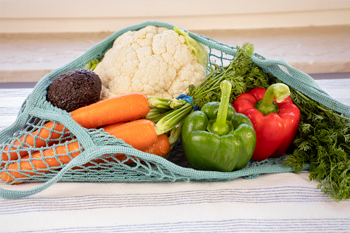 Fresh vegetables in mesh bag on kitchen table. Healthy eating concept. Organic fresh food.