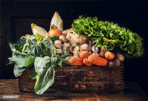 various of fresh vegetables in old  box over dark wooden wall
