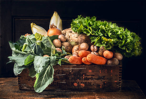 fresh vegetables in old  box over dark wooden wall stock photo