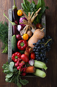 Fresh vegetables in wood crate, food above