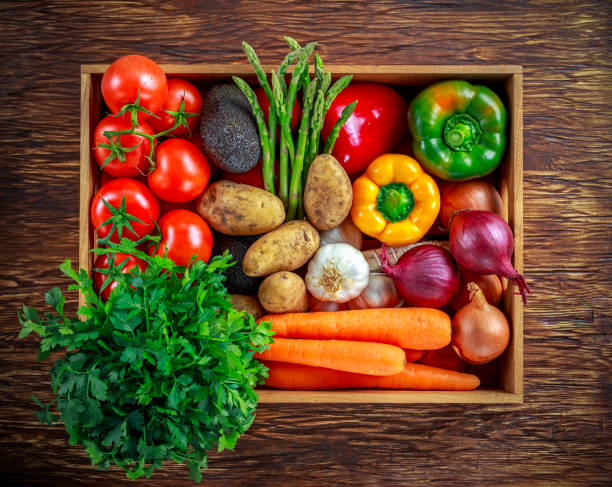 fresh vegetables in wooden box on wooden background - onion juice stock photos and pictures