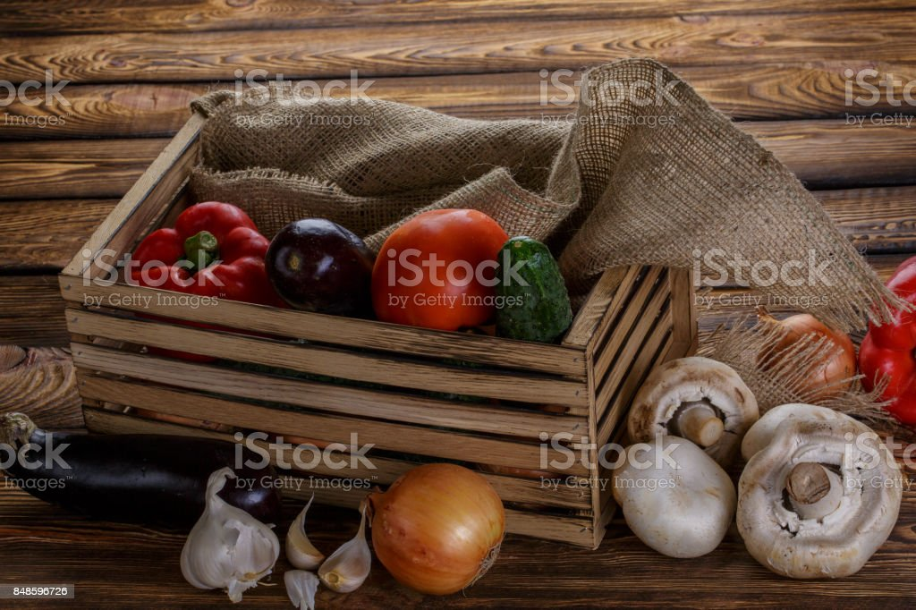 Fresh vegetables in wooden box on wooden background stock photo