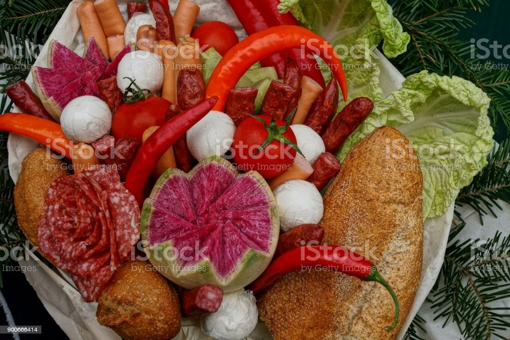 Fresh vegetables of sausage and sausages with pieces of bread in a set with coniferous branches stock photo