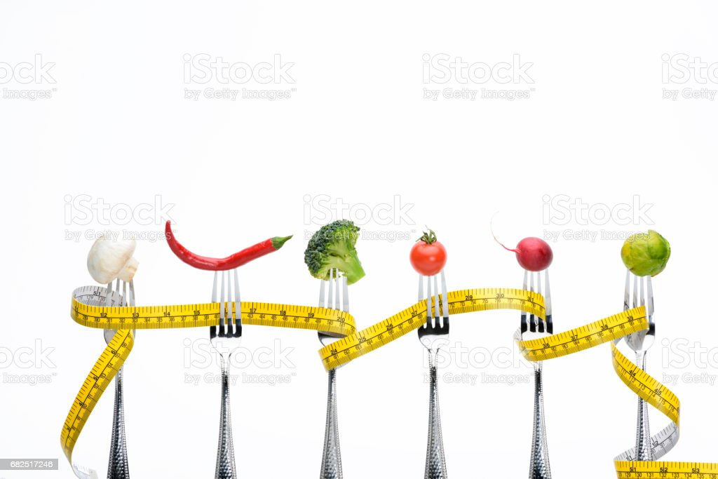 fresh vegetables on forks with measuring tape isolated on white, healthy living concept royalty-free stock photo