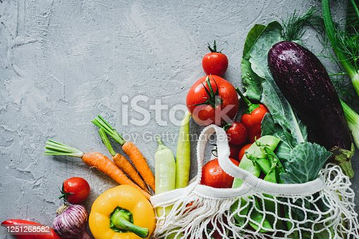 Directly above shot of fresh vegetables in shopping bag. Fresh and healthy groceries on grey background.