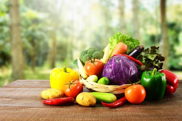 Table en bois et fond nature floue des légumes frais. - Photo