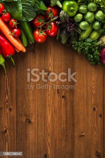 Fresh vegetables on brown wooden background