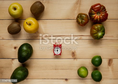 Fresh vegetables and fruits with alarm clock on wood