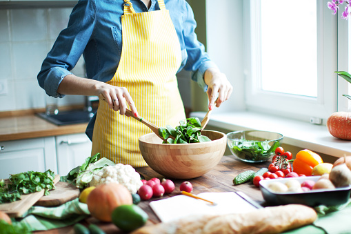 Woman cutting vegetables at the kitchen