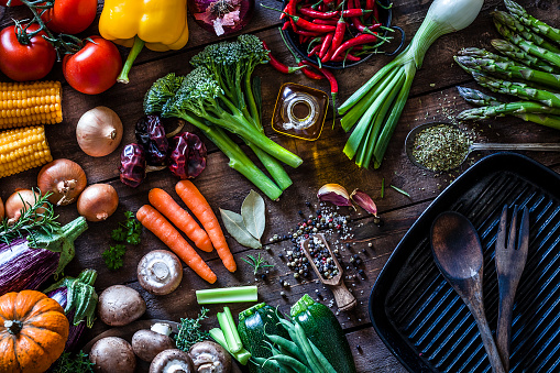 Top view of a rustic wooden table filled with fresh organic vegetables ready for cooking. At the bottom-right is a cast iron pan with a fork and spoon inside. The composition includes garlic, tomatoes, asparagus, edible mushrooms, eggplant, cucumber, broccoli, onion, carrot, corn, and chili peppers. DSRL studio photo taken with Canon EOS 5D Mk II and Canon EF 100mm f/2.8L Macro IS USM