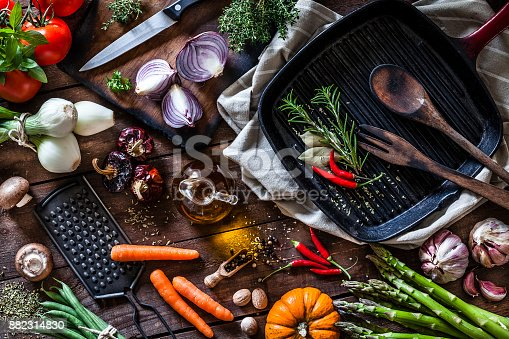 Top view of a rustic wooden table filled with fresh organic vegetables ready for cooking. At the top-right is a cast iron pan and beside it is a cutting board with some spanish onions. The composition includes garlic, tomatoes, asparagus, edible mushrooms, eggplant, cucumber, broccoli, onion, carrot, corn, and chili peppers. DSRL studio photo taken with Canon EOS 5D Mk II and Canon EF 100mm f/2.8L Macro IS USM
