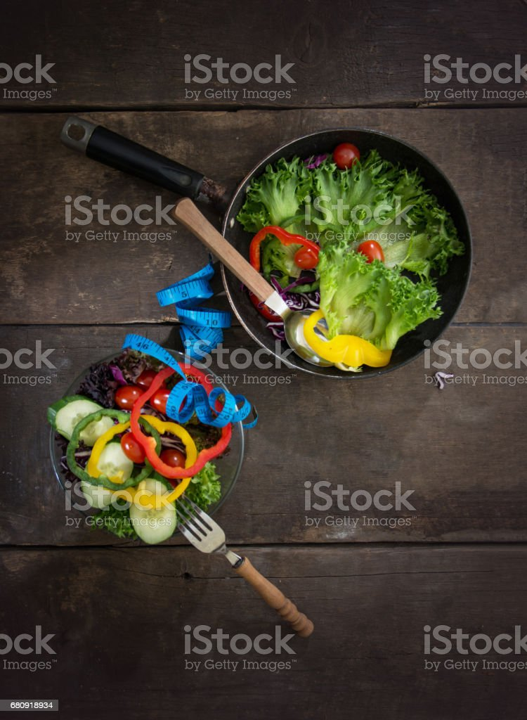 Fresh vegetables salad on the pan and bowl with measuring tape over wooden background. Diet Food and healthy lifestyle concept. royalty-free stock photo