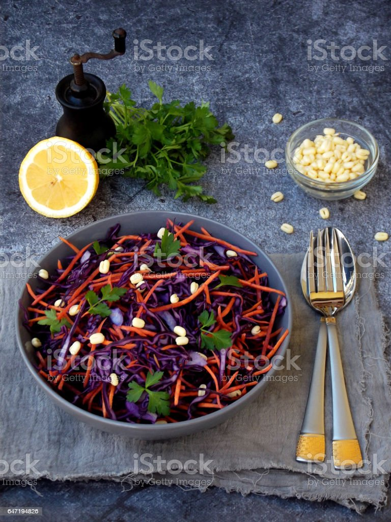 Fresh vegetables salad with purple cabbage, carrot, sprouted mung, parsley on grey clay plate on dark background. Cole Slaw Salad of red cabbage. stock photo