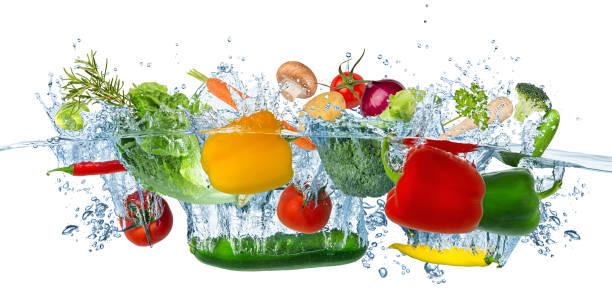 Frisches Gemüse spritzt in blaues klares Wasser spritzt gesunde Ernährung Ernährung Frische Konzept isolierten weißen Hintergrund – Foto