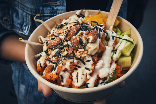 Disposable cardboard bowl with fresh vegetarian salad in hand of a young woman on the street. Every day more and more restaurants offer vegetarian salads as a healthy take out food option.
