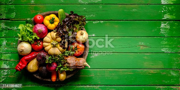 Fresh vibrant colorful organic vegetables in an antique round wooden bowl on an old green wood paneled table background,  atmospheric rustic mood, with good copy space at the right of the image. Vegetables include lettuce, pumpkin, carrot, beetroot, chili, capsicum, onion, tomato, cucumber, avocado and sweet potato.