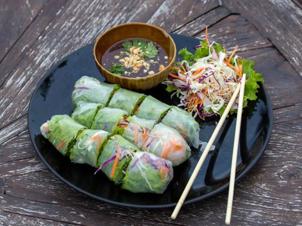 frische frühlingsrollen vietnamesische auf einem teller mit salat - frühlingsrollen stock-fotos und bilder