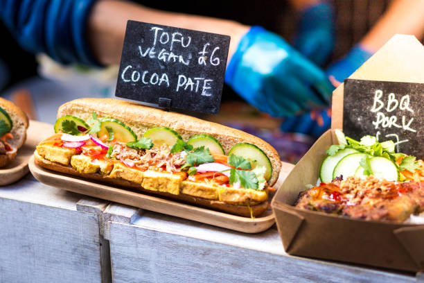 Fresh Vietnamese Vegan Banh Mi Sandwiches for sale at Food Market Close up color image depicting a selection of freshly prepared Vietnamese banh mi sandwiches. Focus is on a tofu vegan sandwich. loaded with different fillings - including chicken and leek - for sale at an outdoor food market in London, UK. People working on the market stall are defocused in the background. Room for copy space. bánh mì sandwich stock pictures, royalty-free photos & images