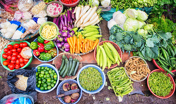 Fresh Vietnamese vegetables fruits spices displayed at Hanoi street market Fresh Vietnamese vegetables, fruits, and spices displayed at  an improvised Hanoi street market on a sidewalk. Each ingredient is in a bowl or basket. vietnamese culture stock pictures, royalty-free photos & images