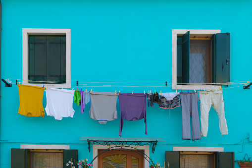 Fresh washed laundry hanging on the blue house in Burano island, Venice
