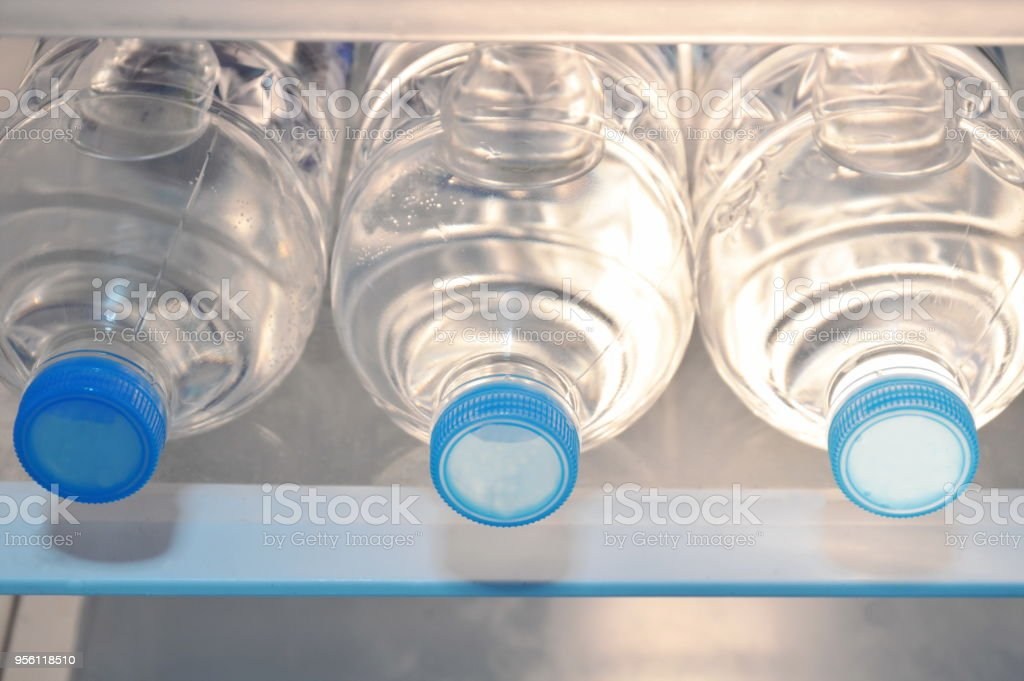 close up of fresh water plastic bottle arranging in refrigerator