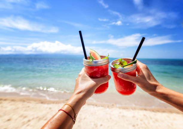 fresh watermelon juice in two glasses against a bright tropical landscape, background of the sea. - summer background стоковые фото и изображения