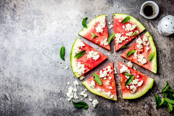 frischwassermelone pizzasalat mit fetakäse, minze, salz und öl auf steinhintergrund - frucht pizza cookies stock-fotos und bilder