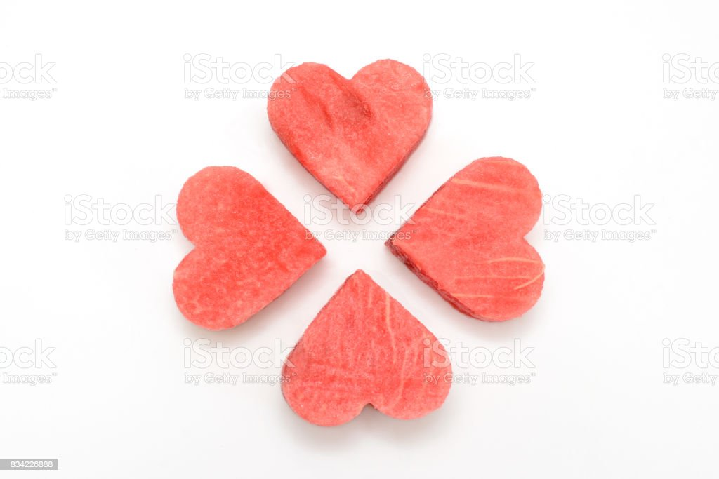 Fresh watermelon slice with carved hearts on white background stock photo