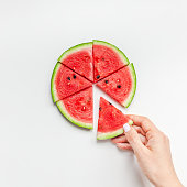 Creative scandinavian style flat lay top view of fresh watermelon slices in woman hands on white table background copy space. Minimal summer fruits creative for blog or recipe book