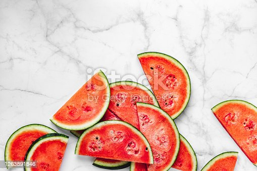 Slices of juicy red watermelon on white background. Fresh watermelon slices on marble surface.