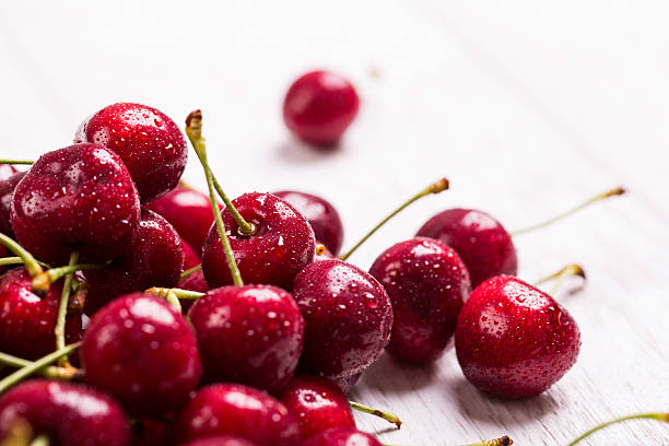 fresh wet cherry on wooden background stock photo
