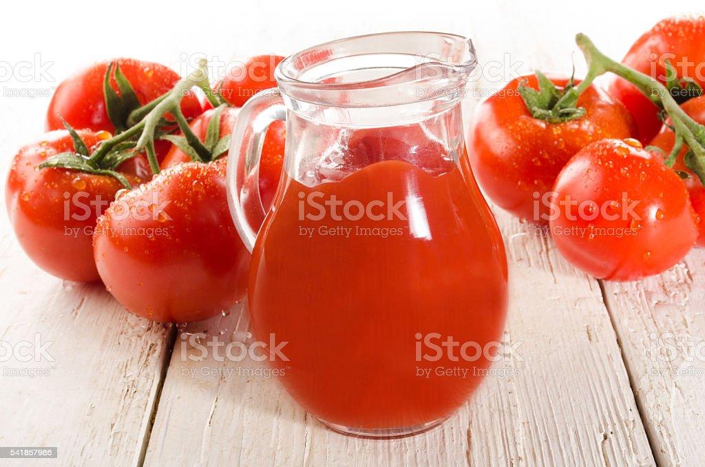 fresh wet tomato on white wood and tomato juice stock photo