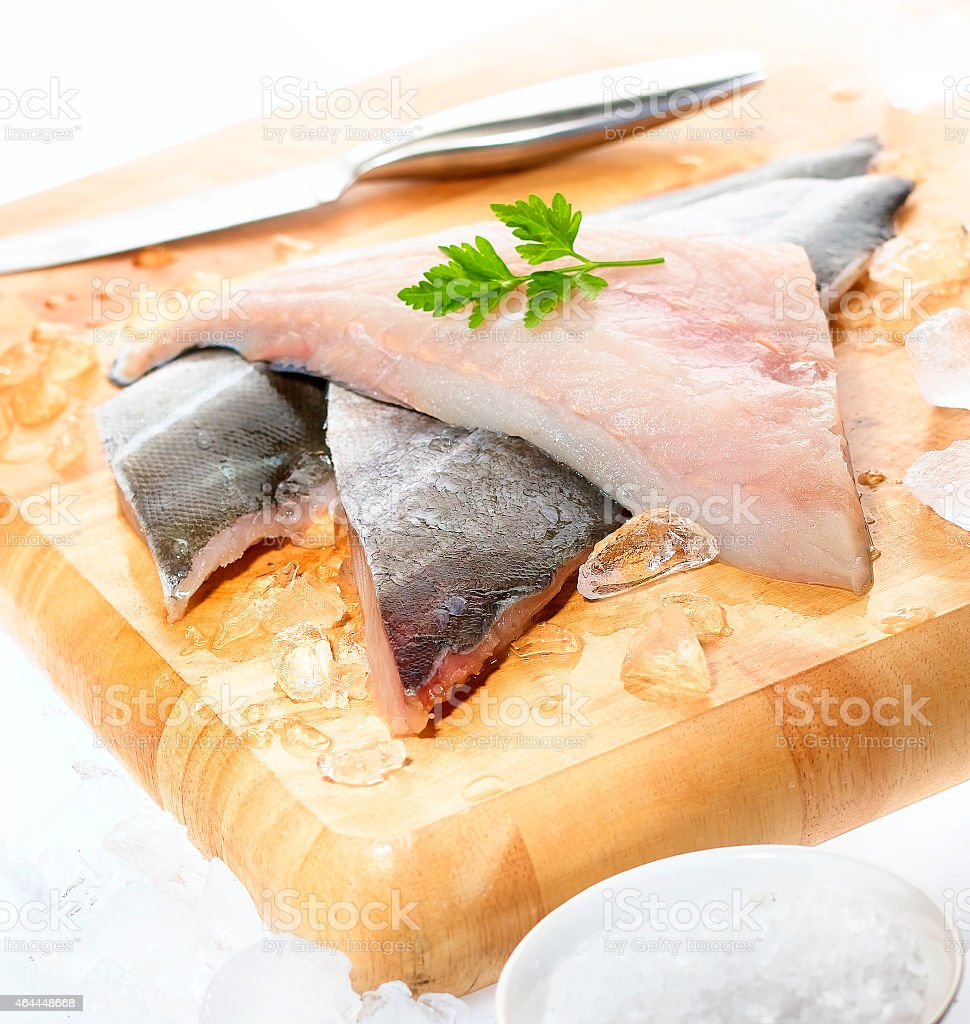 Fresh white fish fillets on chopping board stock photo
