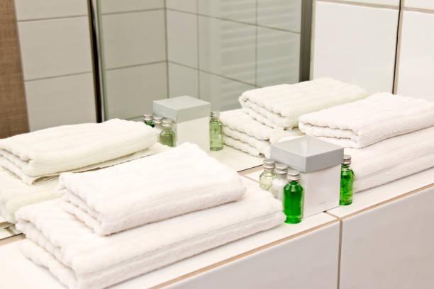 frische weiße gefaltete handtücher mit badezimmer zubehör-set - hausmittel gegen falten stock-fotos und bilder