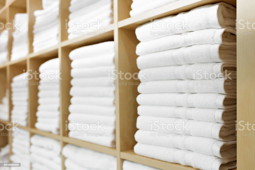 Fresh White Hotel Towels Folded and Stacked on a Shelf - foto stock