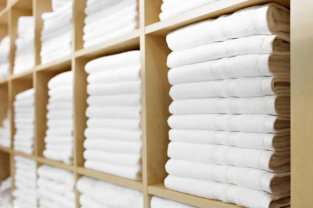 frische weiße hotel handtücher gefaltet und gestapelt auf einem regal - stoffregal stock-fotos und bilder