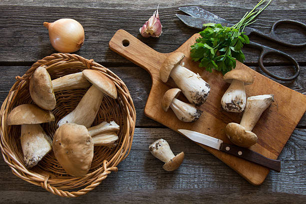 fresh white mushrooms in basket on a rustic wooden board. - 식용 버섯 뉴스 사진 이미지