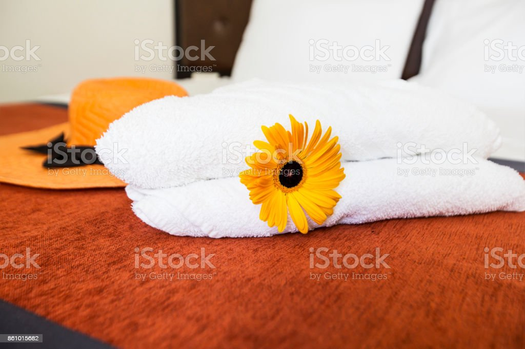 Fresh White Towel With Yellow Flower And Hat On The Bed Room Stock