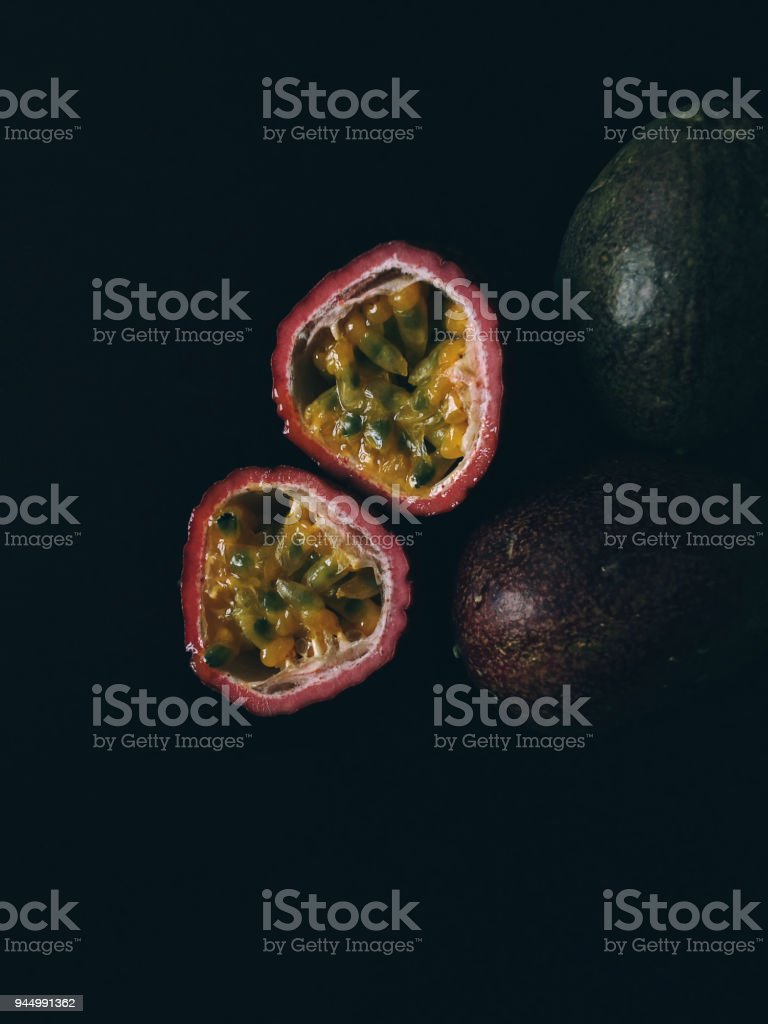 Fresh whole and halved passion fruit over black background stock photo