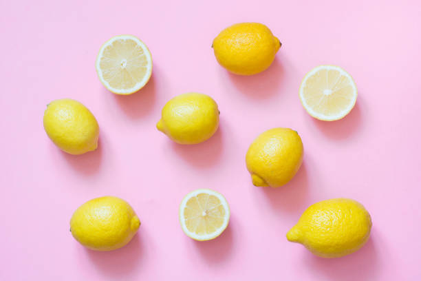 Fresh whole and sliced lemon on pink background. Flat lay. stock photo