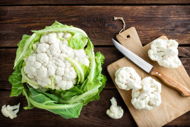 Fresh whole cauliflower on wooden rustic background, top view stock photo