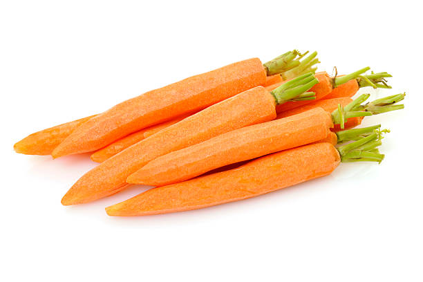 Fresh Whole Peeled Baby Carrots with Green Stems Close Up stock photo