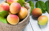 Fresh whole Ripe apricot fruits with a leaf and half in burlap sack on wooden rustic table. Apricots healthy fruit background