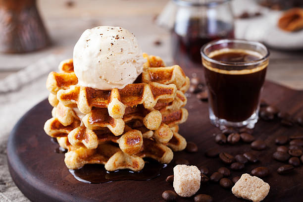Fresh whole wheat waffles, ice cream, maple syrup Fresh whole wheat waffles with ice cream, maple syrup and coffee on a wooden background waffle stock pictures, royalty-free photos & images