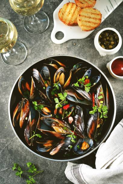 Fresh wild mussels in shells with green onions, garlic, parsley, chili pepper, white wine and olive oil. stock photo