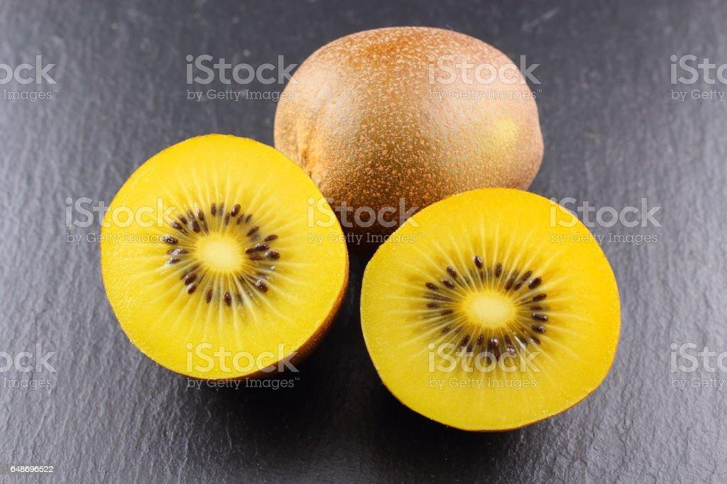 fresh yellow kiwi fruits on a slate plate stock photo