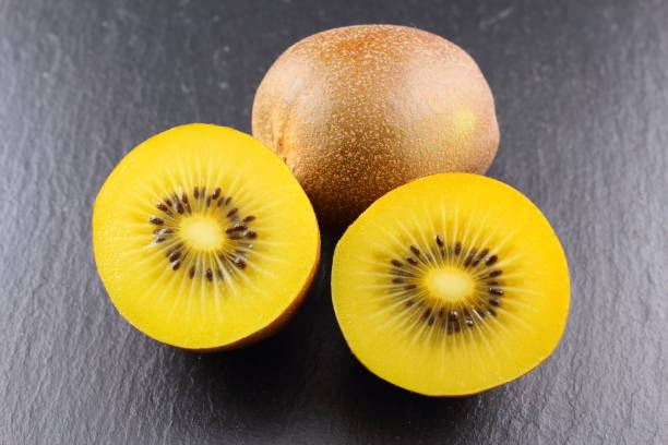 fresh yellow kiwi fruits on a slate plate stock photo