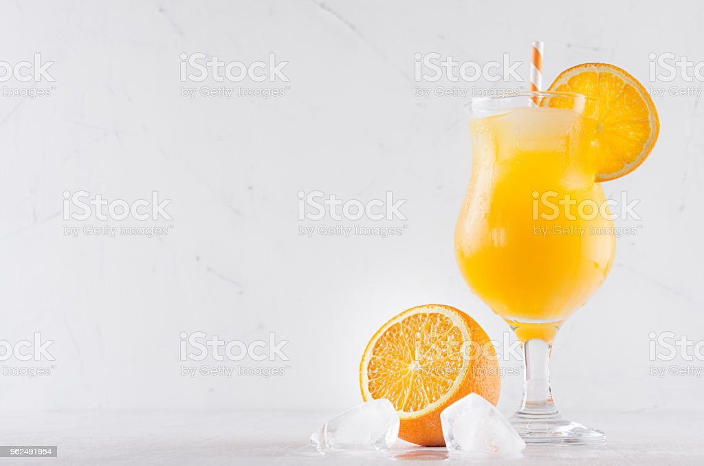 Fresh yellow oranges cocktail in elegance wineglass with ice cubes, straw and half oranges on soft white wood background. - Royalty-free Alcohol Stock Photo