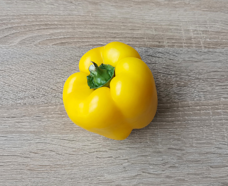 Fresh yellow sweet pepper on a wooden table